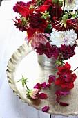 Stillleben mit Blumenstrauss aus Dahlien in Weinrot und Rot auf goldenem Tablett, dekoriert mit Blütenblättern