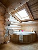 Corner bathtub below skylight in log cabin