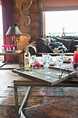 Bottle of wine and glasses on tray on coffee table in log cabin