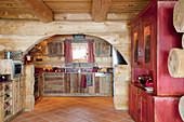 Rustic kitchen with terracotta floor tiles in log cabin