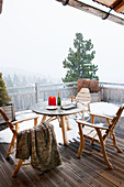 Table and chairs on snowy balcony