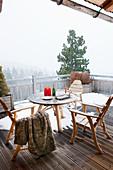 Tisch und Stühle auf dem verschneiten Balkon