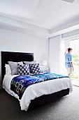Man is standing at the patio door in the bedroom with a black bed