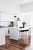 Modern white kitchen with shiny wooden floor
