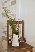 Branches in jug on old wooden chair