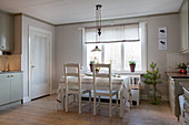 Dining table in cream kitchen-dining room in country-house style
