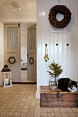 Cat sitting on wooden trunk in country-house-style hallway with double doors and winter decorations