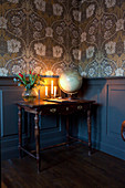 Wooden table against panelled wainscoting and below vintage-style wallpaper
