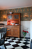 Old dresser against wall with wooden wainscoting and patterned wallpaper