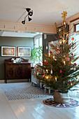 Schlicht geschmückter Weihnachtsbaum im klassischen Wohnzimmer
