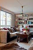 Sofa below window and bookshelves in cosy living room