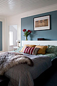 Fur blanket on bed against blue wall panel in bedroom