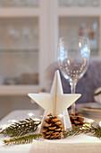Stern, Zweig, Zapfen und Lichterkette als Tischdeko