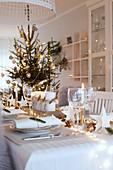 Stimmungsvoll gedeckter Tisch mit Nadelzweigen und Lichterkette an Weihnachten