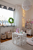 Child's table, play kitchen and bunting in cosy child's bedroom