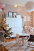 Christmas tree and pompoms in child's bedroom in pastel shades