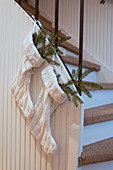 Fir branches in two white knitted Christmas stockings hung from stairs