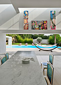 Comic art above open wall between dining room and garden with pool