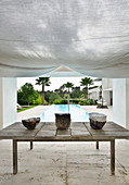 Ceramic bowls on wooden table under awning next to pool