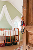 Puppet hung from hand of wooden door leading into vintage-style nursery