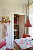Kitchen table and red chairs in front of open pantry door