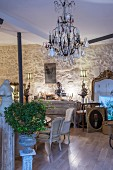 Antiques, crystal chandelier, chest of drawers and gilt-framed mirror on stone wall