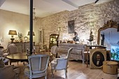 Antique furnishings in renovated period apartment with stone wall