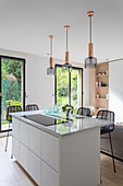 Lamps above island counter in front of floor-to-ceiling windows with garden view