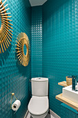Turquoise wall tiles and sunburst mirrors in guest toilet