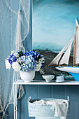 Bouquet of hydrangeas, model of a sailing ship and paintings with a sea motif as a maritime decoration