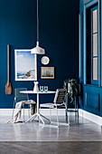 Round bistro table in corner of room with dark blue walls and maritime wall decoration