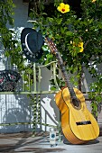 Guitar and hat on garden bench next to flowering hibiscus