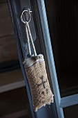 Key fob made from printed hessian hung from door