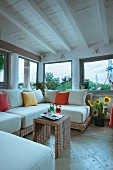 Wicker sofa and colourful scatter cushions in rustic living room