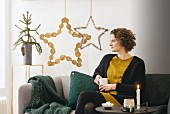 Woman sitting on sofa in front of Christmas stars hand-made from natural materials