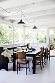 Black dining table with old church bench and chairs in light-flooded dining area