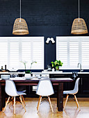 Dining table with replicas of classic chairs for windows and dark blue wall in open kitchen