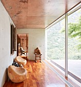 Wooden sculptures in hallway with glass wall, concrete walls and wooden floor