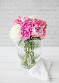 Pink and white peonies in glass vase