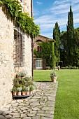 Traditionelle Natursteinfassaden mit Rasenfläche und Zypressen