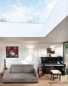Music room with view of sky through glass roof