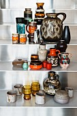 Collection of old seventies vases on metal shelves