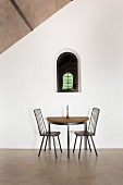 Semicircular table and two chairs below small arched window