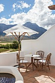 Seating area below parasol and view of mountains