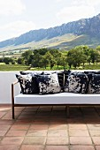 Batik scatter cushions on sofa on terrace with panoramic mountain view