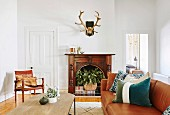 Antlers over an open fireplace with plants in the living room