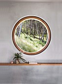 Round window with a view of the forest in a gray wall with a shelf