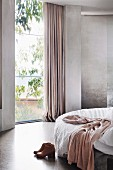 Bedroom in shades of gray with floor-to-ceiling window
