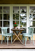 Bistro chairs and folding table on terrace in front of large window