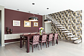 Upholstered chairs in elegant dining area with claret-red wall next to cantilever stairs on wall with patterned wallpaper